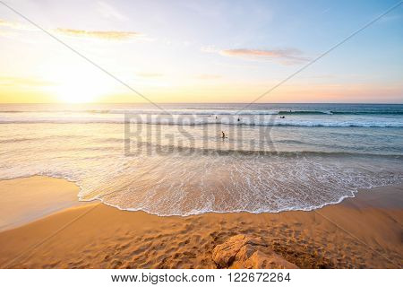 Beautiful beach with surfers swimming near El Cotillo village on Fuerteventura island in Spain