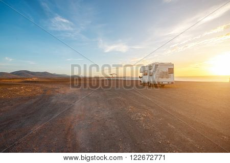 Deserted landscape with camping vehicle on Fuerteventura island in Spain. Wide angle view with copy space