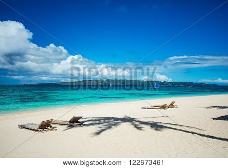 Tropical beach with chaise longues and shadow of palm tree