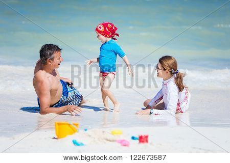 Young happy family of three enjoy beautiful day on the beach