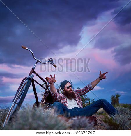 cool bearded traveler making hand gesture beside bike in desert