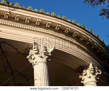 Decorative cresting dentils Corinthian columns and more adorn the roof line and facade of a curved porch on a beautiful old Victorian era home.