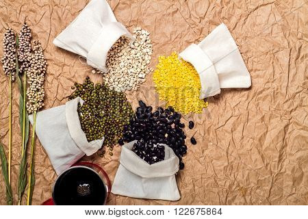 Mixed beans in sack on brown paper background mung bean, soybean, black bean green bean, millet