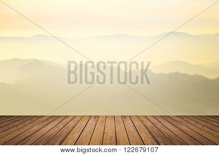 Brown wooden floor with mountain range landscape and beautiful sunrise sky blurred background. use for display or montage products for advertisement in natural summer concept