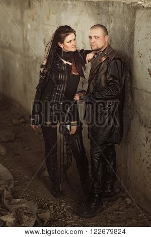Raider man and woman in leather costume with bow at post-apocalyptic world.