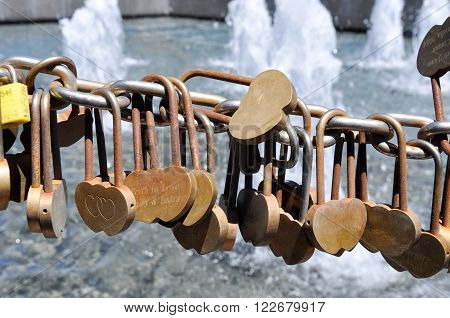 Golden love locks secured to a draped chainlink fence outside the Bell Tower in Perth, Western Australia with a water fountain in the background.