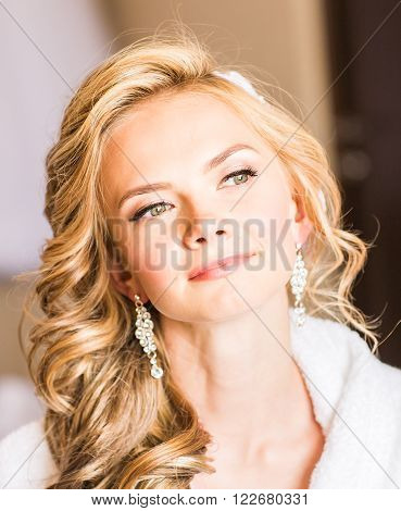 Beautiful young bride with wedding makeup and hairstyle in bedroom, attractive newlywed woman have final preparation for wedding. Happy Bride waiting groom. Marriage Wedding day moment. Bride portrait
