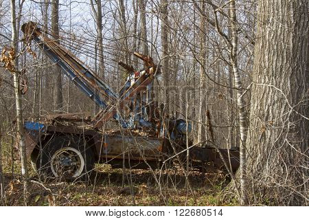 Rusting antique tow truck overgrown with weeds in woods.