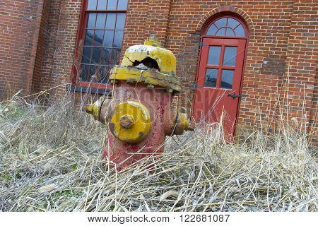 Broken and decaying fire hydrant in weeds outside brick building