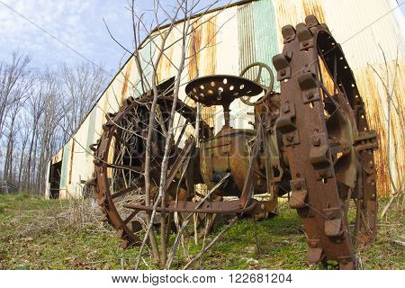Antique metal diesel tractor outside rusting shed.