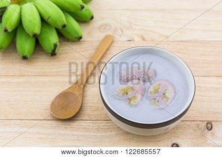 Banana in coconut milk (Kluay Buad Chee) on wood desk Thai desert.