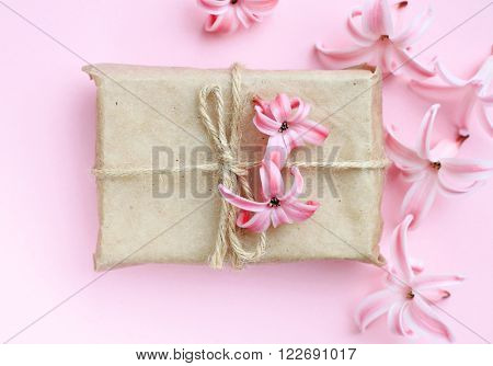Handmade gift wrapping, decorated flowers, pink background. Soft light, soft focus.