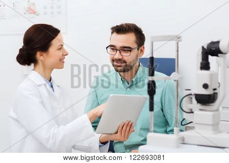 health care, medicine, people, eyesight and technology concept - female optician with tablet pc computer and man in glasses at eye clinic or optics store