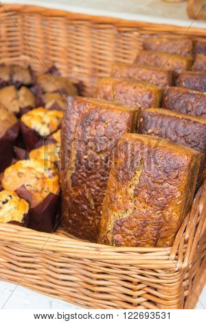 Heap of freshly baked traditional loaves of rye bread in wicker basket on stall at the bazaar