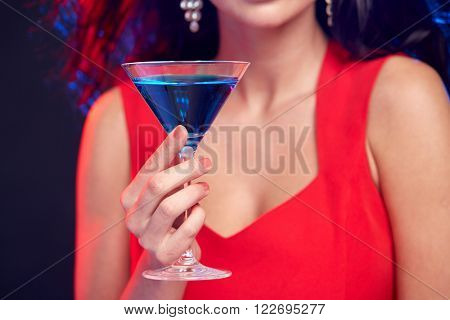 people, holidays, party, alcohol and leisure concept - close up of woman with cocktail at nightclub