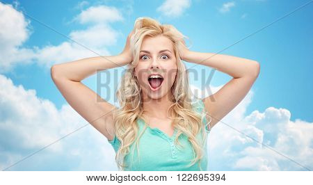 emotions, expressions, hairstyle and people concept - smiling young woman or teenage girl holding to her head or touching hair over blue sky and clouds background