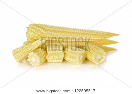 whole and cut baby corn on white background