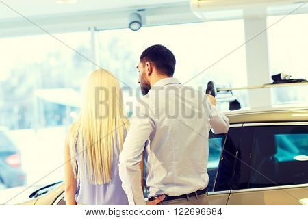 auto business, car sale, consumerism and people concept - couple buying car in auto show or salon from back