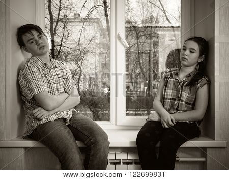 Sad teenager boy and girl sitting on a window sill.