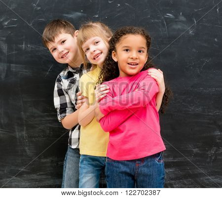 three different children stand one by one peeking out from behind each other
