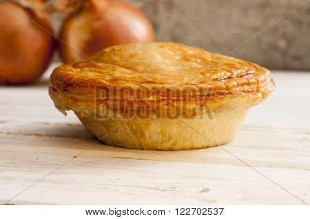 Cooked Pie And Onions On A Smooth Wooden Surface