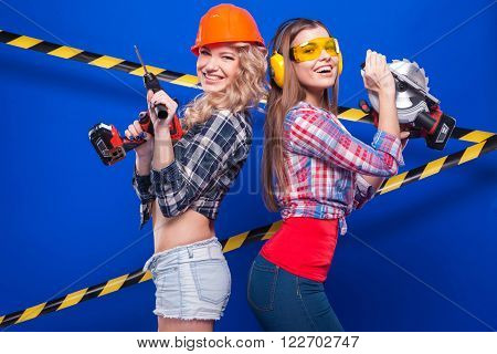 Girl Builder In The Construction Helmet And Goggles With A Construction Tool On A Blue Background