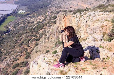 woman in a black tracksuit photographing sitting on the edge of the cliff