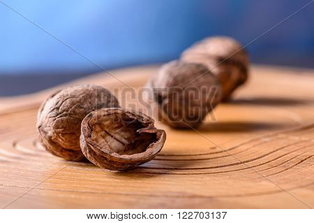 Three ripe whole walnuts in shell, one half of walnut. closeup on a wooden surface ** Note: Shallow depth of field