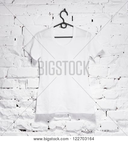 brick whitewashed wall with white shirt on hanger