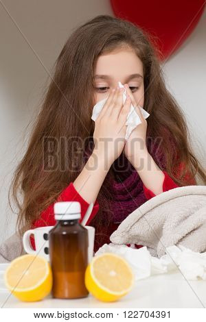 Fever, cold and flu concepts. Little girl sneezing in to tissue. Lady blowing her nose while sitting on her bed at home.