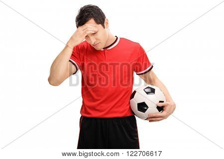Young sad football player holding a ball and looking down isolated on white background