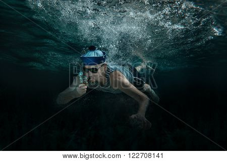 Man swimming under water and smokes a pipe.