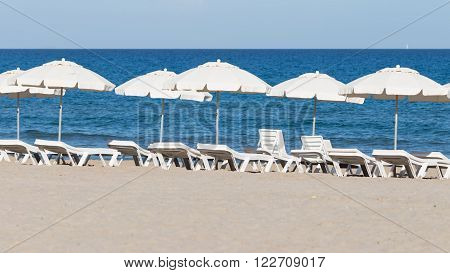 many white parasols and deck chairs on the sandy beach of pure white sand and blue sea and sky