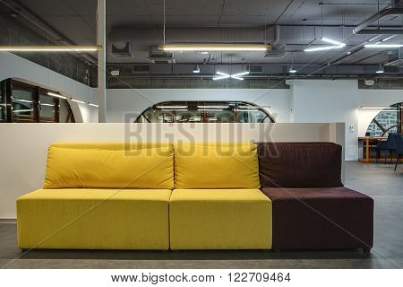 Yellow-brown sofa with pillows on the white low wall background. Behind the sofa there is a hall in a loft style with white walls and brown rounded windows. Upper parts of wall are concrete. On the floor there are gray tiles. At the top there are communic