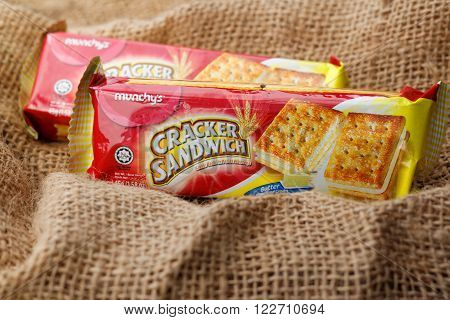 JOHOR,MALAYSIA - March 15th 2016: Mini-packs of Munchy's cream cracker on sackcloth. Munchy's is a food manufacturer based in Malaysia.