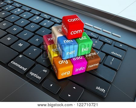 Domain name cubes standing on laptop computer keyboard.