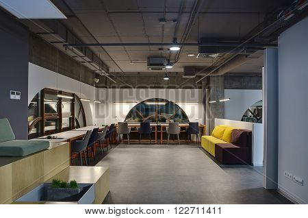 Hall in a loft style with white walls with brown rounded windows. Upper parts of walls are concrete. Close to windows there are light tables with orange legs and gray and blue chairs. Between the tables there are niches with plants and pen holders. Opposi