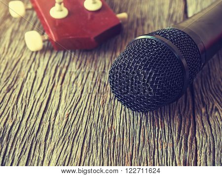 Black microphone on wooden plate with guitar in out of focus background.: Vintage style and filtered process.