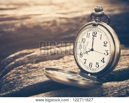Retro pocket watch with antique number is showing 8 o'clock on wooden background. Vintage style and filtered process.