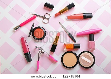 Decorative makeup cosmetics and manicure tools on the pink background