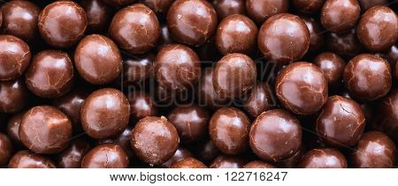 Brown chocolate dragee balls background close up top view letterbox format
