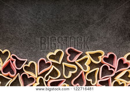 Red and yellow heart shaped pasta top view copy space food background