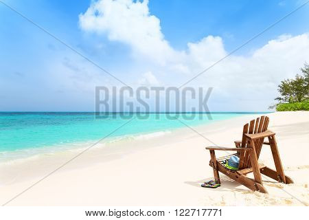Lonely beach chair with hat and slippers at tropical beach summer holiday concept
