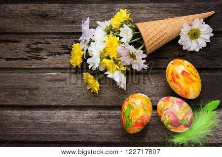 Easter background with eggs flowers and decoration on wooden board top view