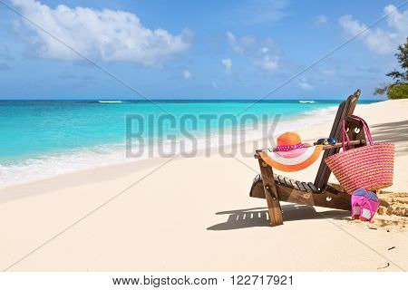 Resting Chair with bag hat flip-flops and sunglasses on sunny beach tropical beach vacation and travel concept
