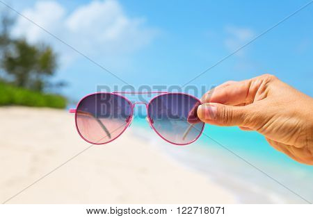 A hand holding sunglasses on beautiful tropical beach background