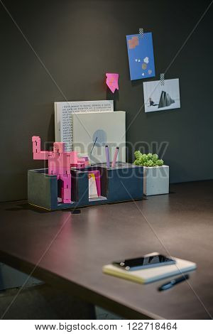 Dark table on a background of a dark board with stickers. On the table there are holders with pens and notebooks and a pink robot, plant in a pot, notebook with phone on it and a pen.