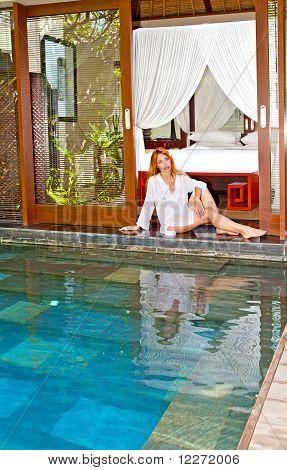La bella joven está en el umbral de una casa de campo en una salida en la piscina