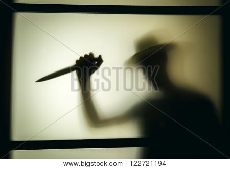 Killer with a knife in her hand. Shadowy figure behind glass
