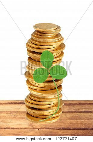 gold coins stack and clover leaf on table isolated on white background